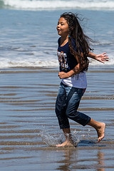 Young Hispanic girl with long black hair runs ...